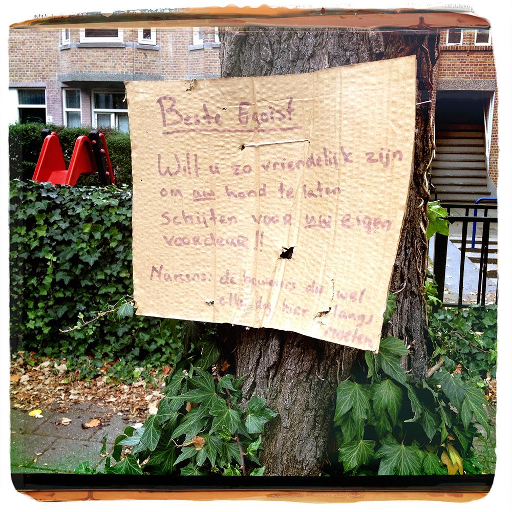 Straattekst nr. 14 Stuk karton aan boom met quasi keurig geformuleerd verzoek aan hondeneigenaar om beest voor eigen deur te laten schijten