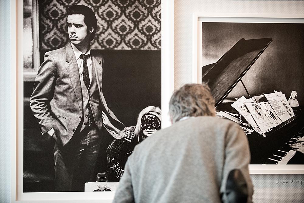 Bezoeker bekijkt bijschrift bij door Corbijn gemaakte portretten van Nick Cave?
