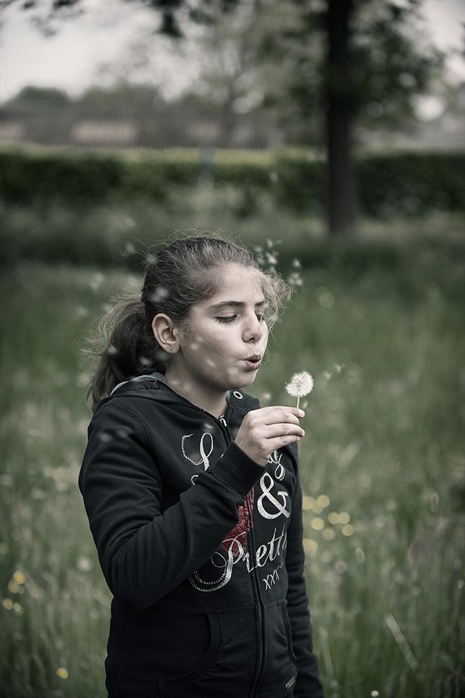 Perla uit Syrië blaast een paardenbloem leeg en doet een wens...